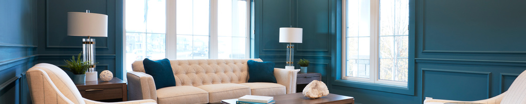 A teal living room with casings around the windows and panel moulding around the walls.