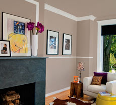 A living room with a light brown walls and white baseboards, chair rails and crowns.